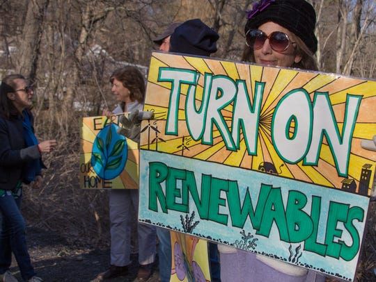 Diane Hawlk holds a sign displaying one of the environmental