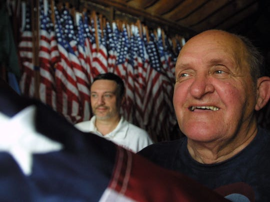 Keith Oakley, co-chairperson, left, and John E. Biegel, Jr, chairman of the Clifton Avenue Of Flags in the Clifton City Hall grounds barn where flags are stored. Photo from July 2, 2003.