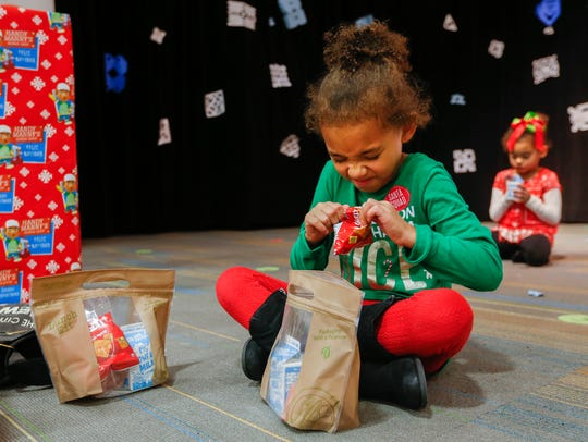 Kaydence Parker, left, struggles to open a bag of Cheez-Its