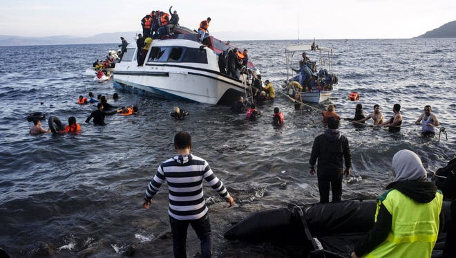 Volunteers and local residents help refugees and migrants disembark from a small vessel after their arrival in Skala Sykaminias on the northeastern Greek island of Lesbos on Oct. 30/