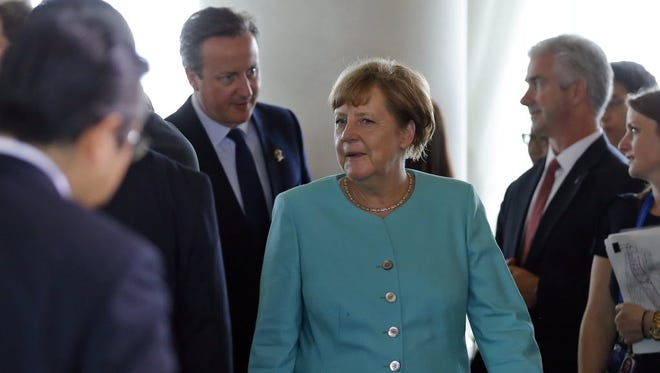 German Chancellor Angela Merkel, center, and British Prime Minister David Cameron, left, arrive for a working session during the 2016 G-7 Summit in Shima, Japan.
