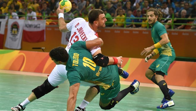 Poland's pivot Bartosz Jurecki (L) vies with Brazil's right back Jose Guilherme de Toledo during the men's preliminaries Group B handball match Poland vs Brazil at the Rio 2016 Olympics Games at the Future Arena in on Sunday.