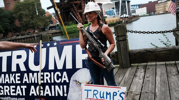 A Donald Trump supporter poses with a gun while attending