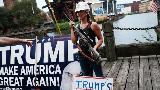 A Donald Trump supporter poses with a gun while attending a rally for Trump on the first day of the Republican National Convention in July