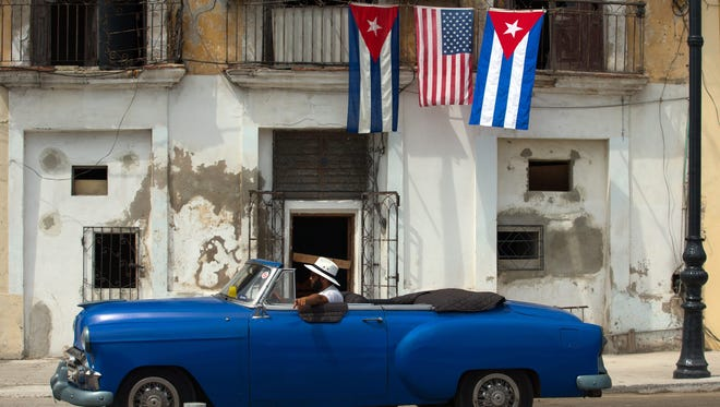 An old car passes by a house decorated with the flags of the United States and Cuba in Havana, Cuba, on March 20, 2016, as the island is preparing for the visit of US President Barack Obama. (EPA/ORLANDO BARRIA)