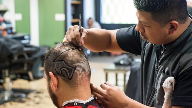 """Fidel Ramirez, of Diversified Cuts in Hanover, touches up the Philadelphia Eagles logo on """"die-hard Eagles fan"""" Jose Beltran's head on Feb. 2, 2018."""