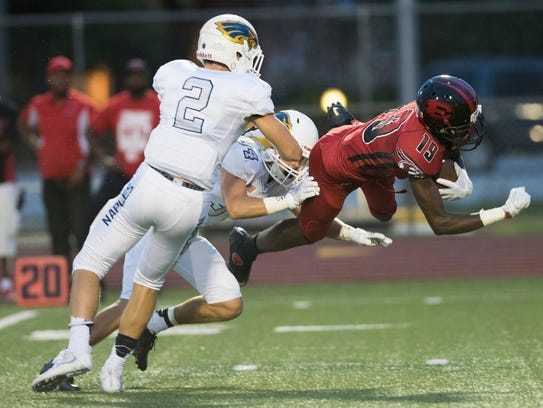 Joshua Ultima of Miami-Edison is tackled by Brady Weber