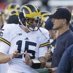Michigan quarterback Jake Rudock (15) speaks head coach Jim Harbaugh