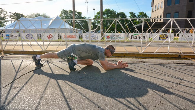 Nathan Agen of Seymour stretches prior to the start of the 40th edition of the Bellin Run on June 11, 2016. Stretching before and after running is key to preventing injuries.