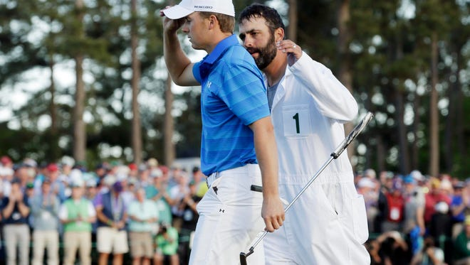 Jordan Spieth walks off the 18th green with caddie Michael Greller after the final round of the 2016 The Masters golf tournament at Augusta National Golf Club on Sunday.