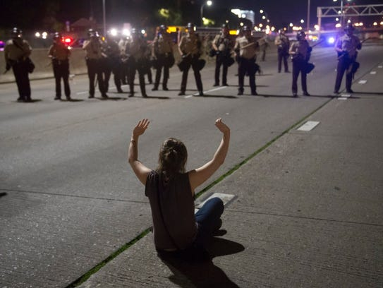 A protester sits in front of a line of police after