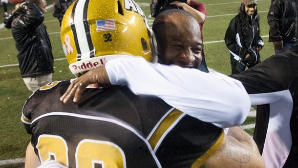 Alabama State coach Brian Jenkins hugs linebacker Kourtney