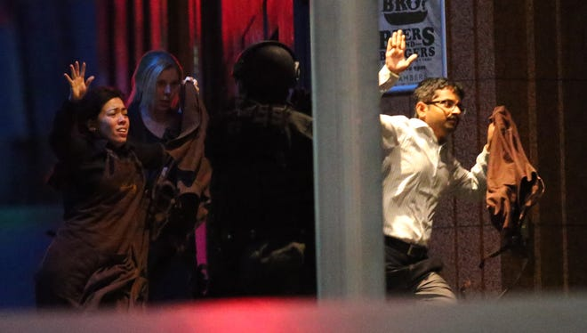 Hostages run towards police from a cafe under siege at Martin Place in the central business district of Sydney, Australia, on Tuesday.