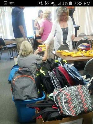 Denise Dangel hands backpack supplies to Sharon Kaska.
