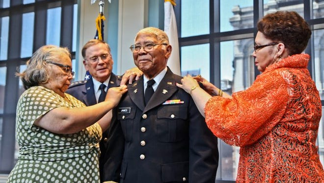 John Edward James Jr., an Army veteran of World War II, is pinned with the rank of second lieutenant by his daughters Brenda Roberta Watts (left) and Dr. Marion Teresa Lane.