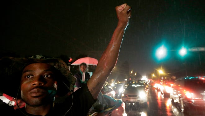 A protester holds up a clenched fist Friday in front of a convenience store that was looted and burned following the shooting death of Michael Brown by police nearly a week ago in Ferguson, Mo.  A suburban St. Louis police chief on Friday identified the officer whose fatal shooting ignited days of heated protests, and released documents alleging the teen was killed after a robbery in which he was suspected of stealing a box of cigars.