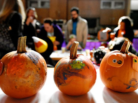 Decorated pumpkins dry on a table while more are painted