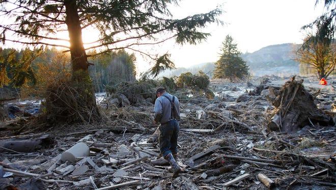 Steve Skaglund walks across the rubble on the east side of Saturday's fatal mudslide near Oso, Wash., Sunday.