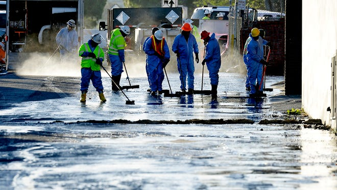 Workers clean a street after 10,000 gallons of crude oil spilled from a burst pipe in Los Angeles.