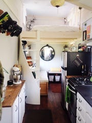 The main living area of Chrissy Bellmyer's Essex area tiny house, which features a spiral staircase leading to the sleeping loft.
