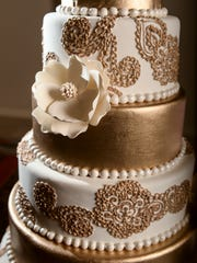 A golden traditionally-themed wedding cake, created