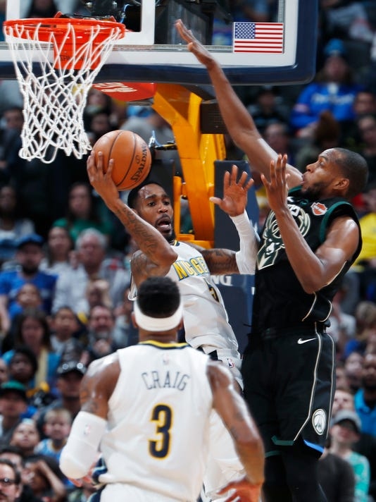 Denver Nuggets forward Will Barton, left, looks to pass the ball as Milwaukee Bucks guard Eric Bledsoe defends during the first half of an NBA basketball game Sunday, April 1, 2018, in Denver. (AP Photo/David Zalubowski)