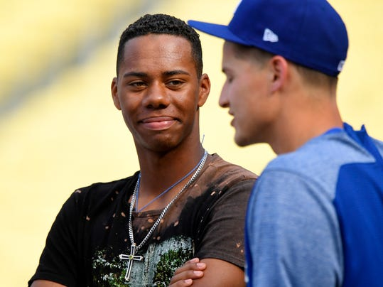 FILE - In this April 28, 2017, file photo, high school baseball pitcher Hunter Greene, left, talks with Los Angeles Dodgers shortstop Corey Seager prior to a baseball game between the Dodgers and the Philadelphia Phillies, Friday, April 28, 2017, in Los Angeles. Greene has piqued lots of interest from teams picking early in the Major League Baseball draft, including the Twins. (AP Photo/Mark J. Terrill, File)