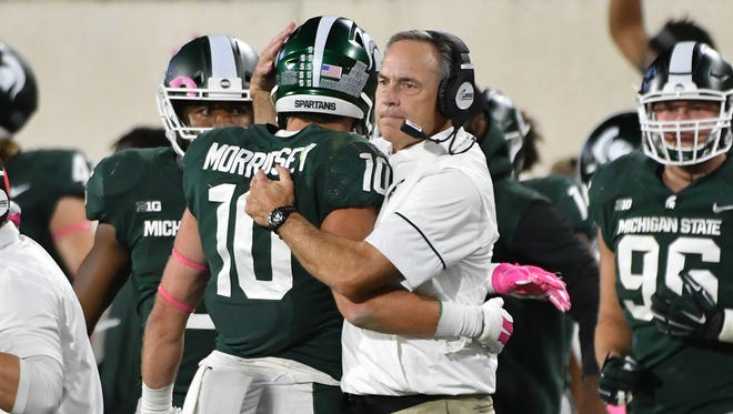 Michigan State head coach Mark Dantonio hugs his players, including Matt Morrissey, after stopping Indiana on fourth down so the Spartans could run out the clock.