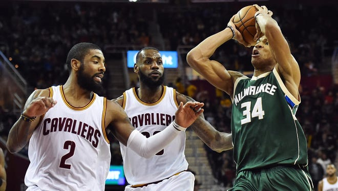 Bucks forward Giannis Antetokounmpo drives to the basket against Cavaliers guard Kyrie Irving (left) and forward LeBron James (center).