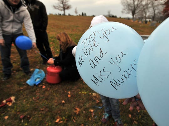 Friends and family members of Josh Barnes wrote messages on balloons before releasing them near his grave Nov. 13, 2014, at Maple Grove Cemetery in Lancaster.
