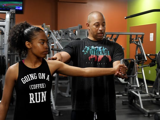 Rodney Stephenson shows his 16-year-old daughter Nylah proper form a pulley machine during a morning training session at Anytime Fitness, in Jackson, Tuesday, June 12. Nylah, who will be a senior in high school in Georgia, runs track and trains with her dad during the summer.