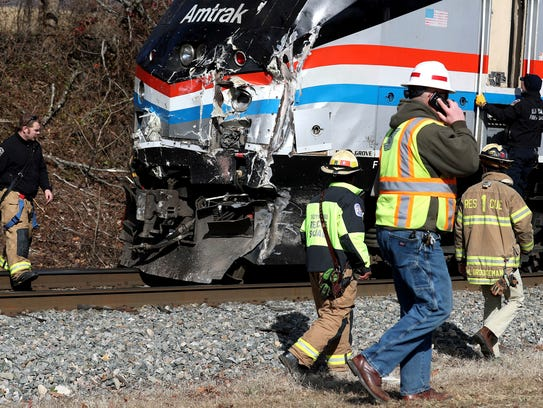 Emergency personnel inspect the lead engine of an Amtrak