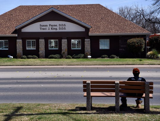 Anthony Randle waits for the bus March 21 on Buffalo Gap Blvd. He said he had never before noticed the interesting name of the dental office across the street.