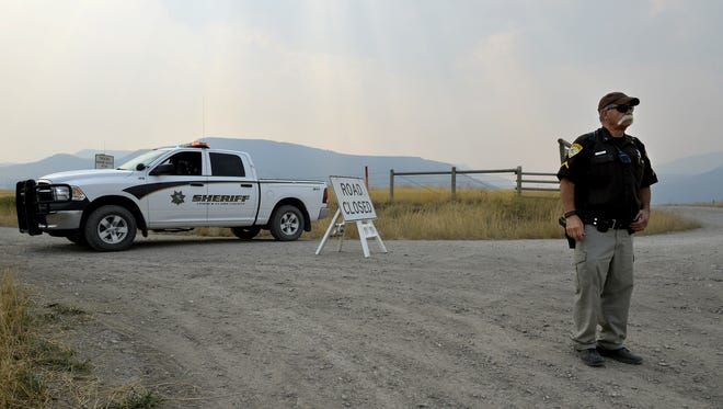 Reserve Deputy Dennis Corbett with the Lewis and Clark County Sheriff's Department mans the intersection of Flat Creek Road and Highway 434 as the Alice Creek fire continues to grow on Tuesday afternoon south of Augusta.