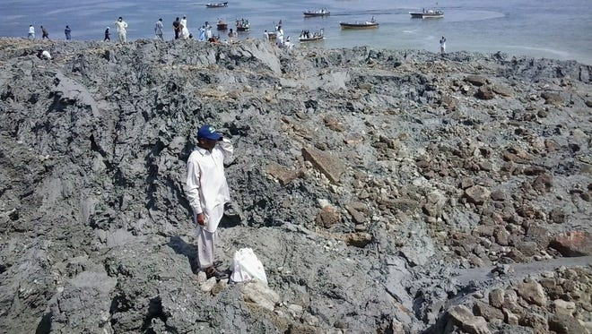 Pakistani residents gather on an island that appeared off the coastline of Gwadar after an earthquake on Sept. 25, 2013.