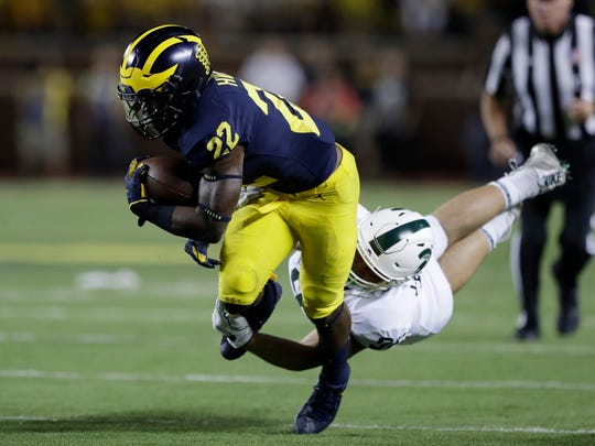 Michigan's Karan Higdon is tackled by Michigan State's Jacub Panasiuk on Oct. 7, 2017, in Ann Arbor.