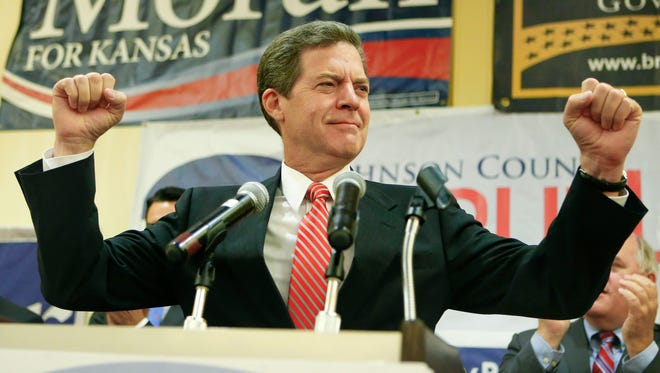 Kansas Gov. Sam Brownback pumps his fists as he greets the crowd on Aug. 5, 2014, at a Republican gathering in the Overland Park, Kan.