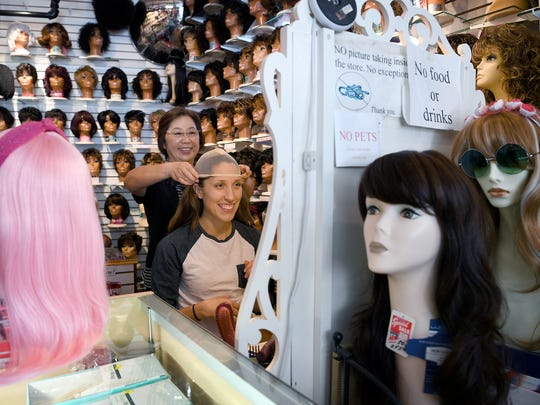 Sandy Kanupp helps Kaitlyn Merrels with a wig cap so