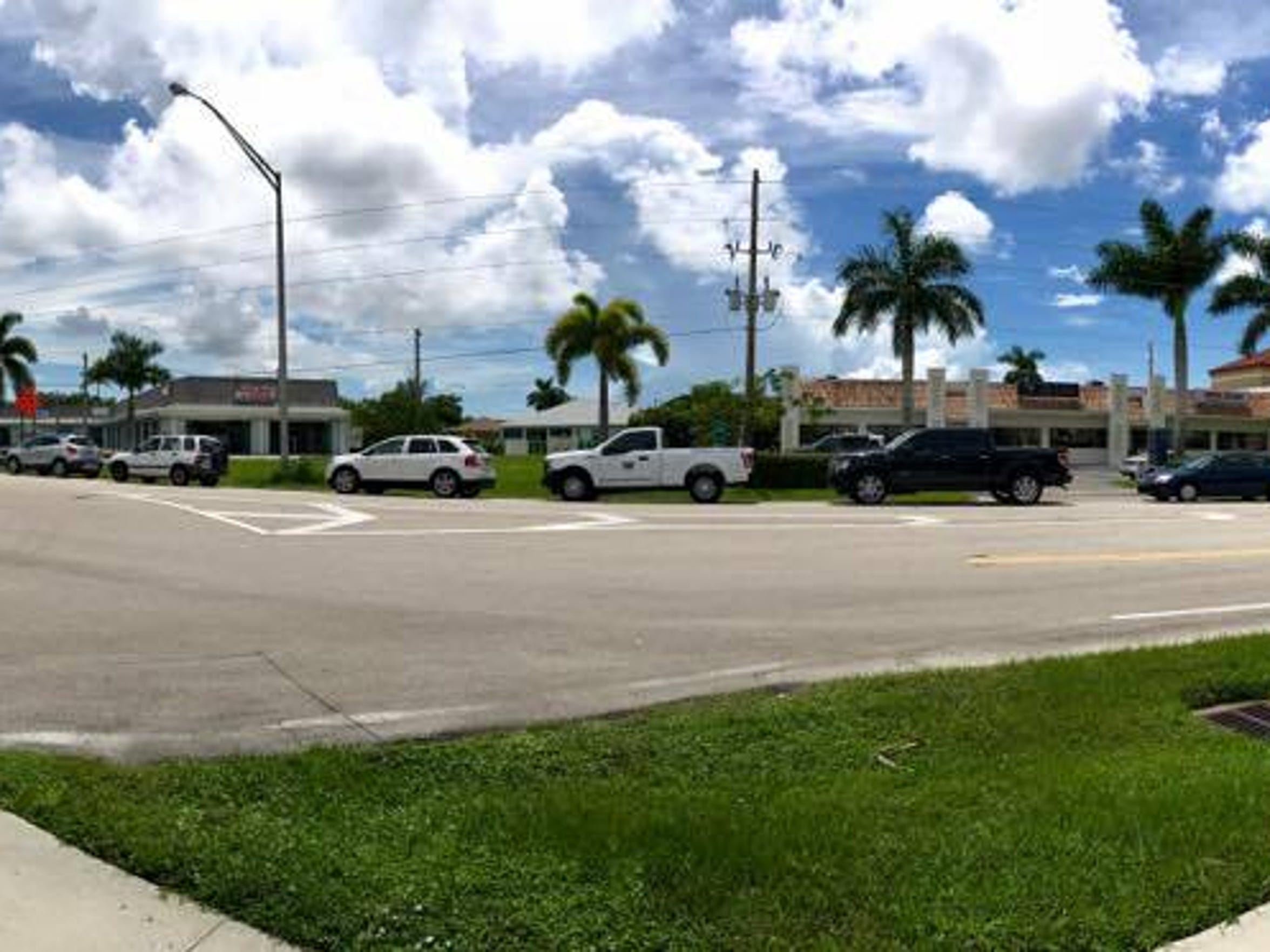 A panoramic photo of cars lined up down the street