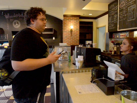 Brandon Stodden orders food from Woodstock Bakeshop, Friday evening. Stodden, who is a first-time customer to the restaurant, participated in the Pokemon Go night in downtown Jackson.