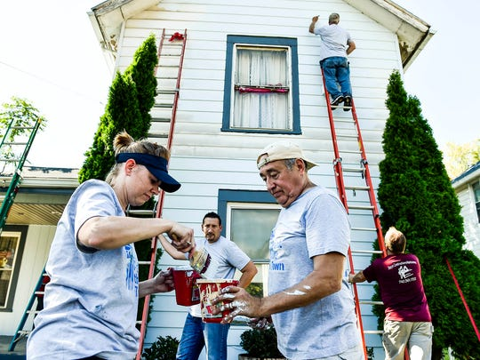 Kristi Reed (left) pours paint into a container for Vaughn Sizemore (right) as their group for Paint the Town finishes up for the day on a house on Olney Avenue. The crew started their day around 830 in the morning and despite the heat didn't let up throughout the day.