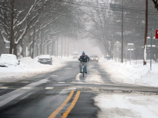 A man hops on his bike Wednesday to head north on Hoffman