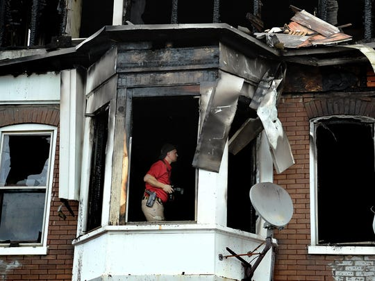 A fire investigator takes photos inside a row house
