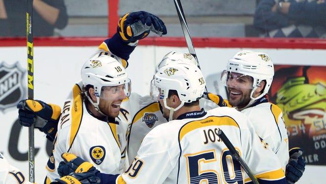 Predators James Neal, left, celebrates a third-period goal with teammates Saturday.