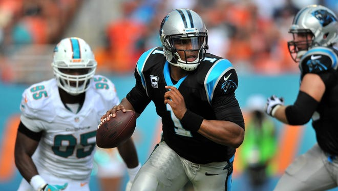 Carolina Panthers quarterback Cam Newton (1) scrambles as Miami Dolphins defensive end Dion Jordan (95) chases during the second quarter at Sun Life Stadium in Miami on Nov. 24, 2013.