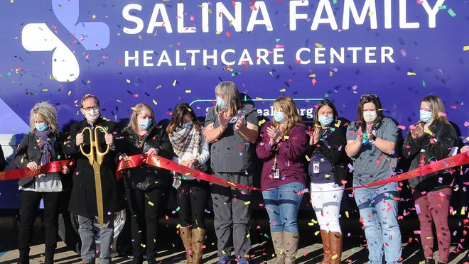 Dr. Robert Kraft, CEO and chief medical officer at Salina Family Healthcare Center, SFHC, cuts the red ribbon as the staff members applaud in front of the new mobile health unit on Thursday afternoon. The mobile health unit has two slide-outs and will be used for a COVID-19 mobile testing site and will eventually be used as an immunization center, mobile medical unit and dental outreach vehicle throughout the Salina community.