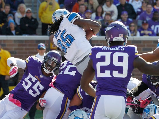 Detroit Lions running back Joique Bell (35) leaps over the Minnesota Vikings defensive line to score from the 1-yard line during the second half of an NFL football game Sunday, Oct. 12, 2014, in Minneapolis. (AP Photo/Ann Heisenfelt)