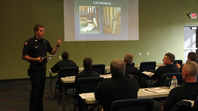 Eric Doyle (left), a training instructor for West Lafayette Fire Department, trains first responders Wednesday on safe sleep practices for infants.