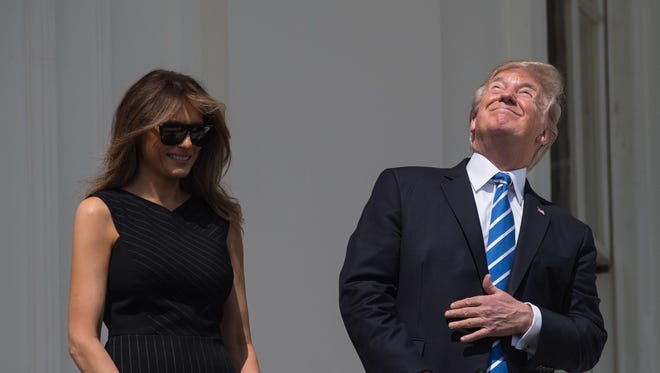 U.S. President Donald Trump and First Lady Melania Trump look up at the partial solar eclipse from the balcony of the White House in Washington, DC, on August 21, 2017.