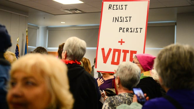 Individuals gather and have signs during the Women's March Anniversary Celebration on Sunday, Jan. 21, 2018 at the Lewes Library in Lewes, Del.